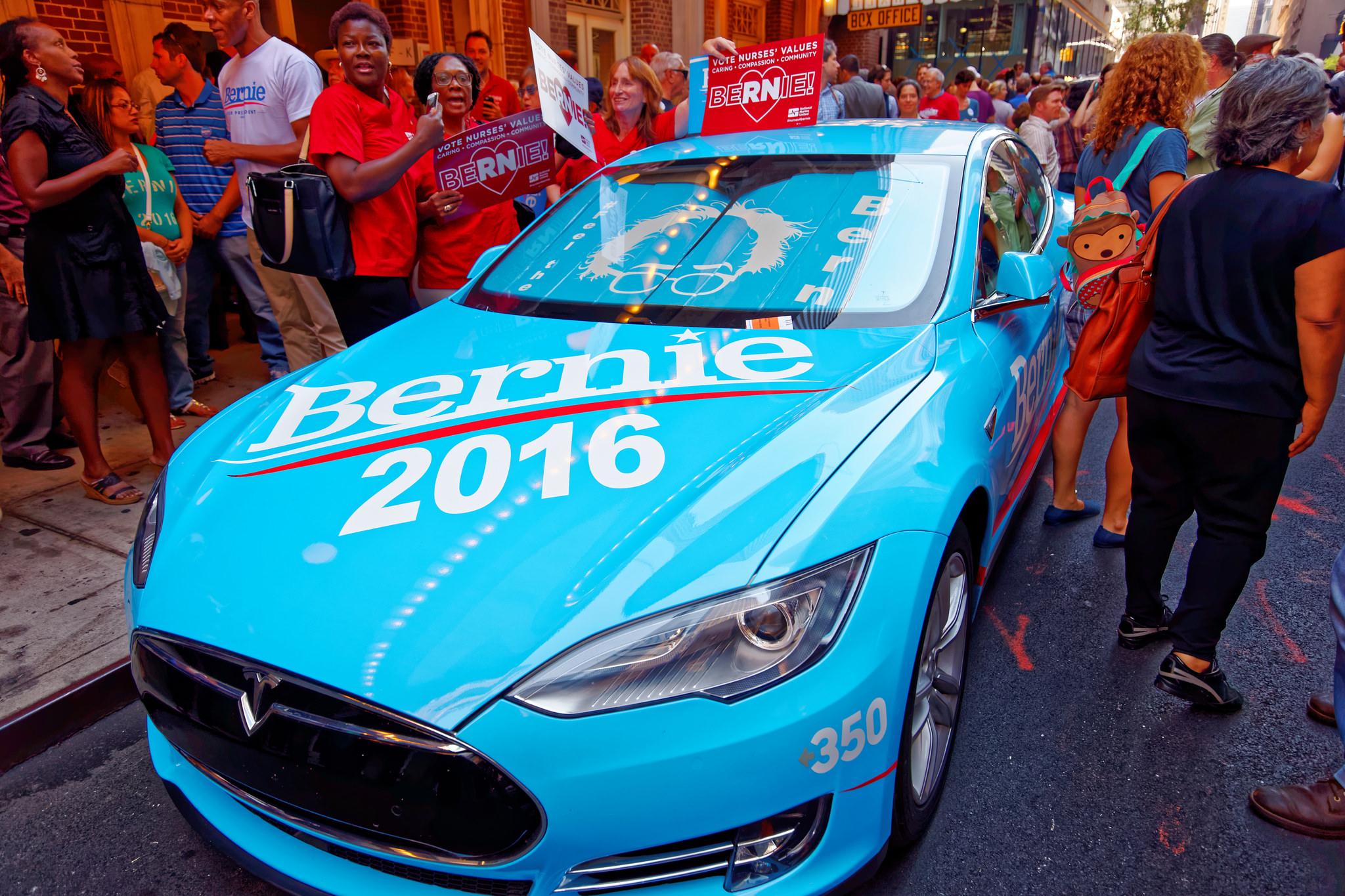 Bernieanhängare med en Tesla, som inte tillverkas i klassiska amerikanska bilstaden Detroit, Michigan  utan i Silicon Valley. (Foto: Michael Vadon. CC BY-SA 2.0)